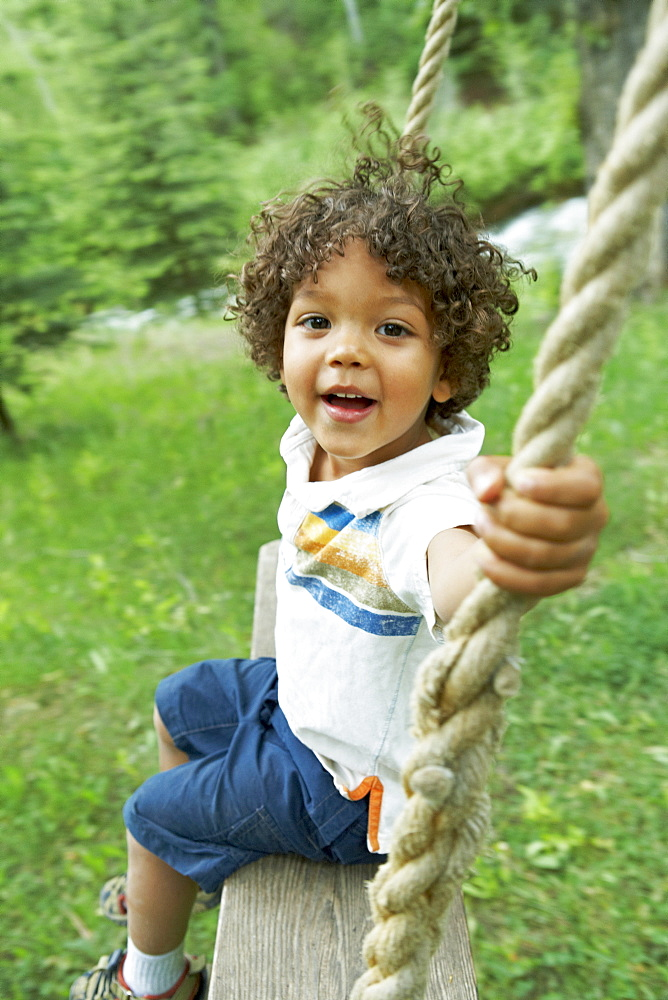Cute young child sitting on swing