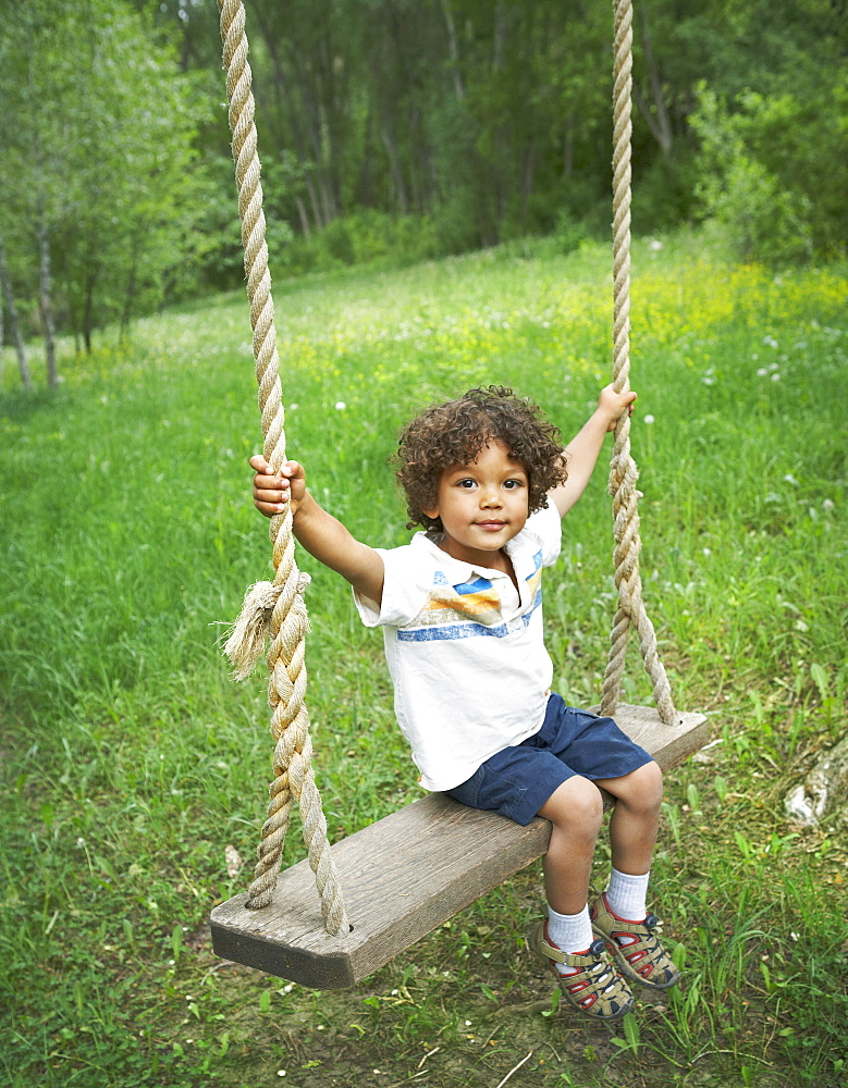 Young child sitting on large outdoor swing