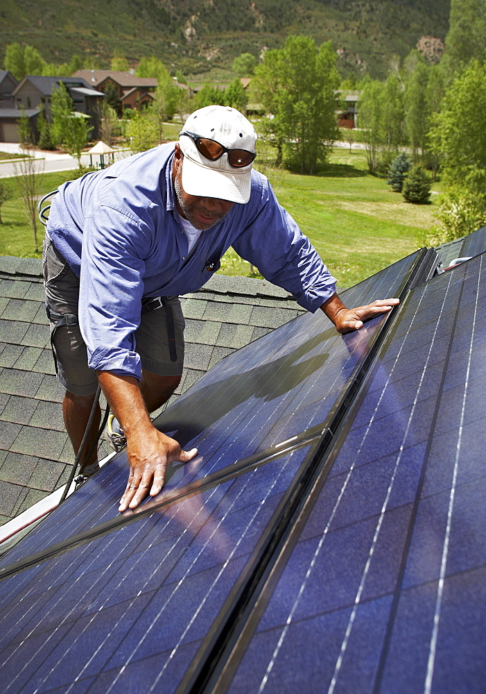 Construction worker installing solar panel on roof - 1178-11713