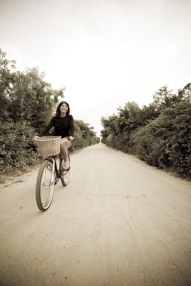 Woman biking on small rural road
