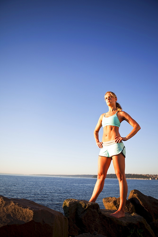 Athletic woman standing by the ocean