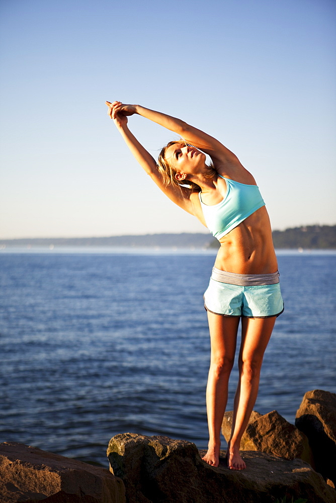 Athletic woman stretching by the ocean