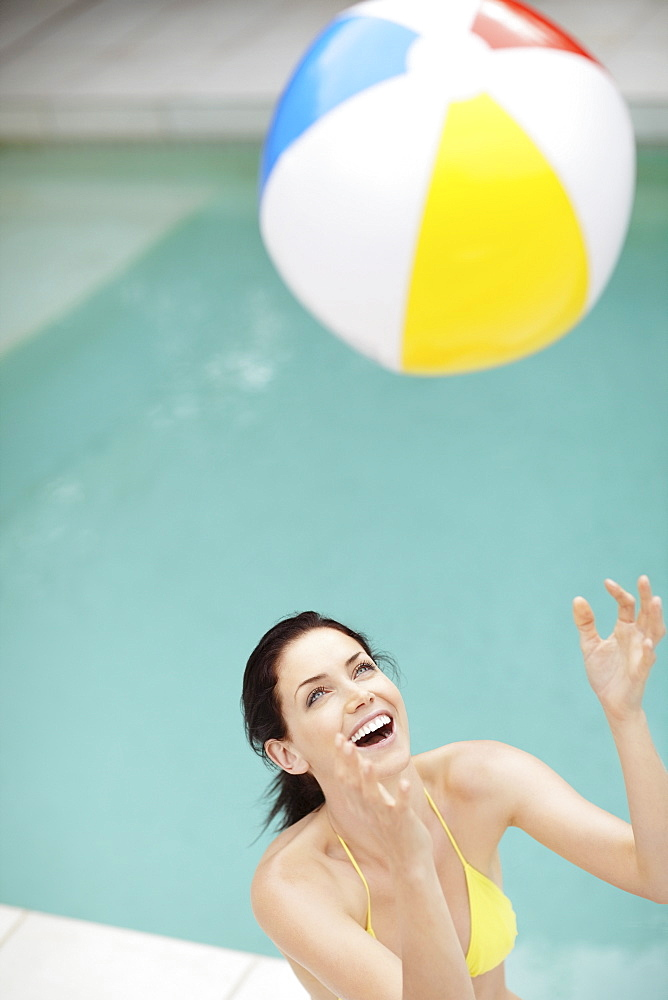 Attractive brunette playing with a beach ball