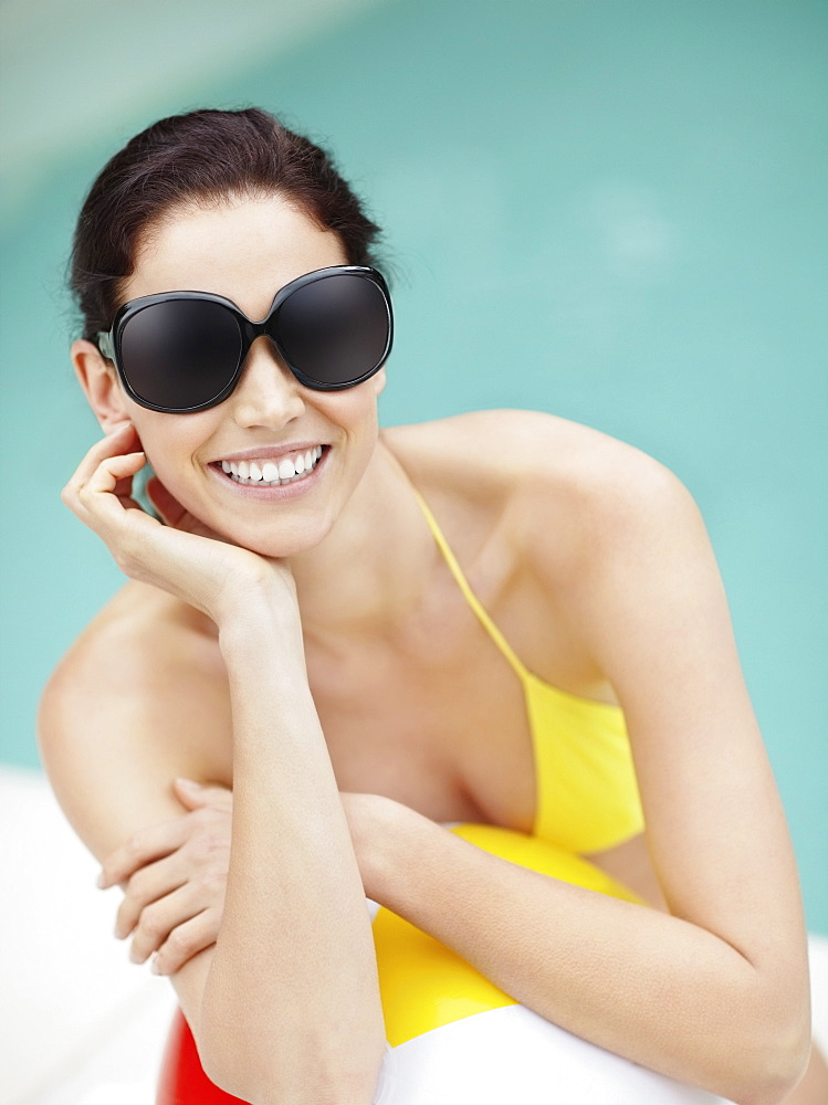 Attractive brunette wearing sunglasses and bikini