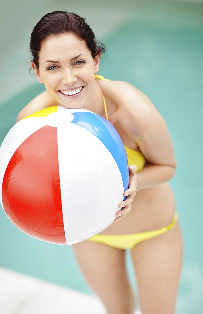 Attractive brunette holding a beach ball