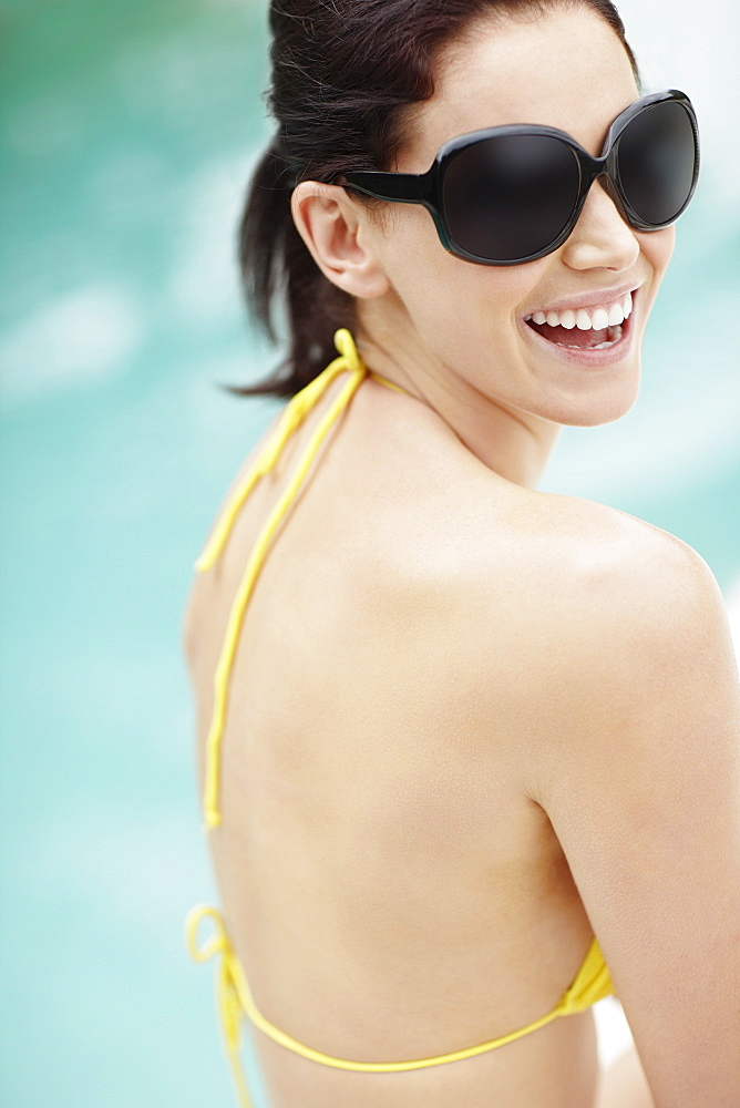 Laughing brunette wearing sunglasses and bikini