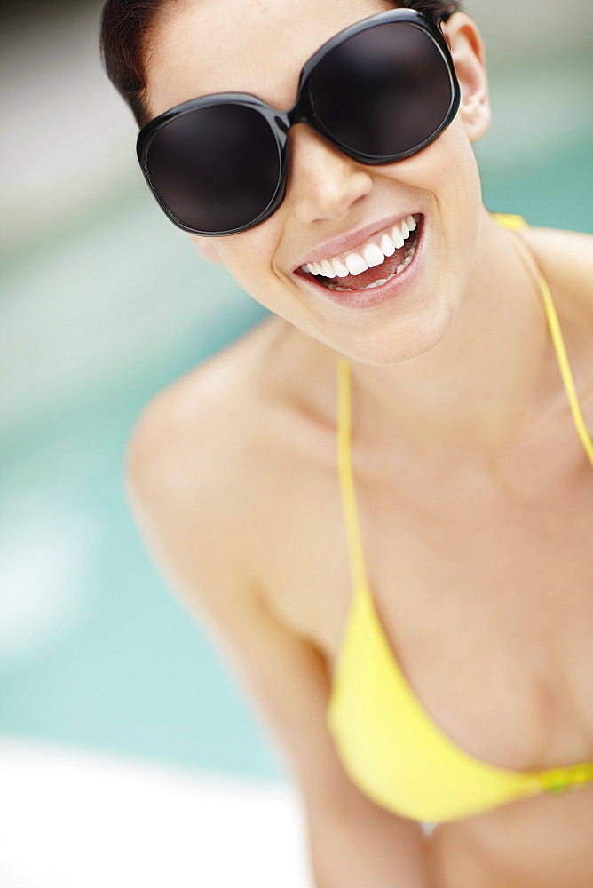 Smiling woman wearing bikini and sunglasses