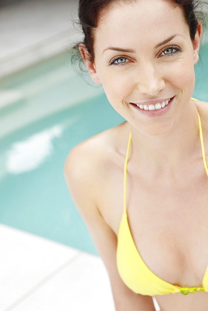 Bikini clad woman standing next to pool