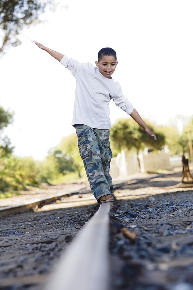 Boy walking on railroad track