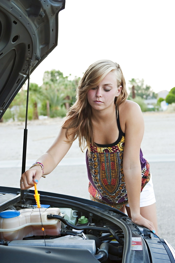 Woman checking car's oil