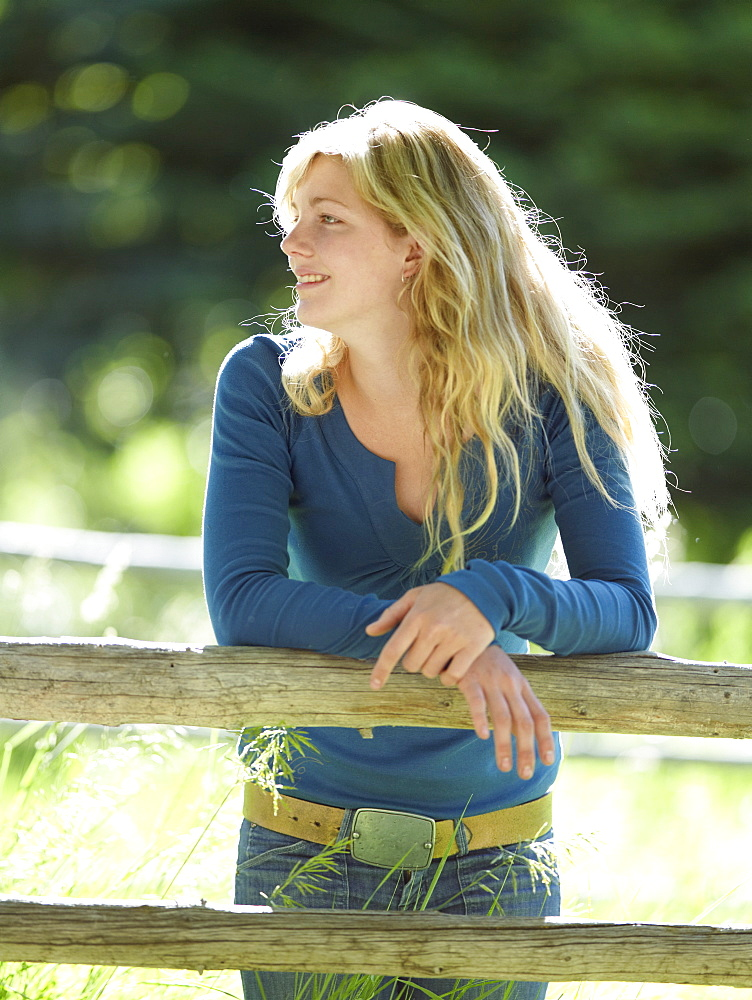 Young woman leaning on fence