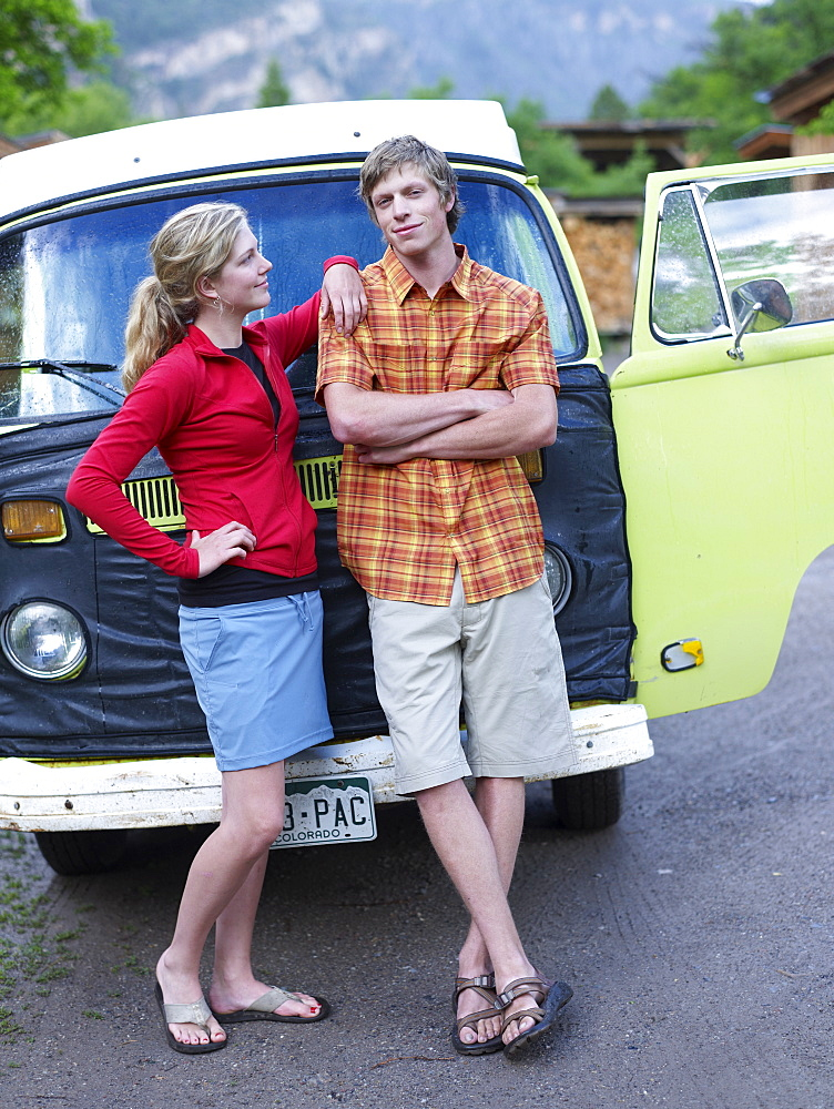 Young couple standing in front of van