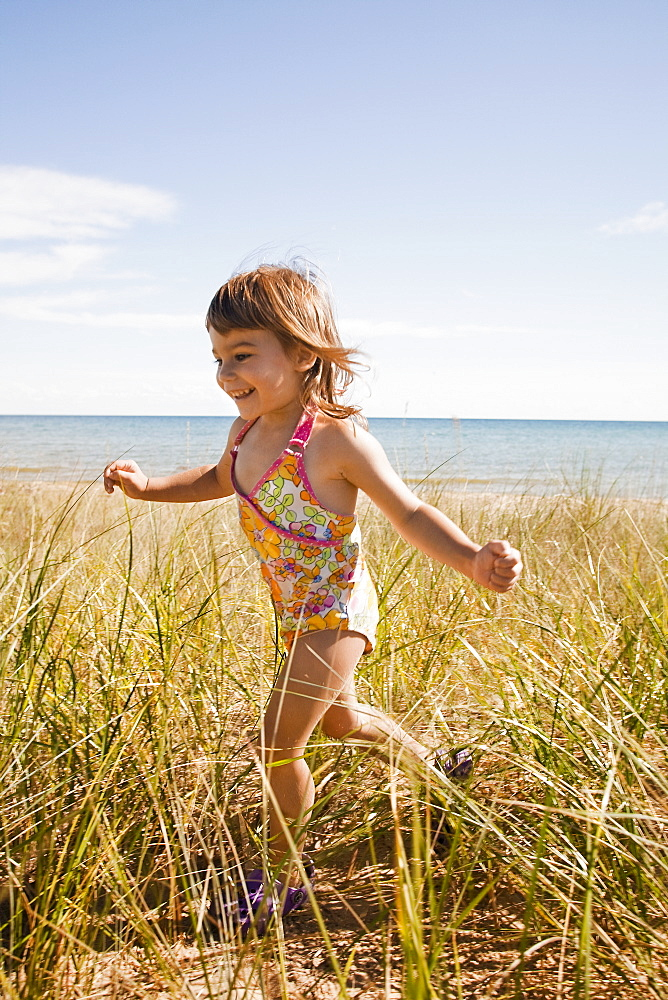 Beaver Island, Girl running in grass on beach, Beaver Island, Michigan, USA