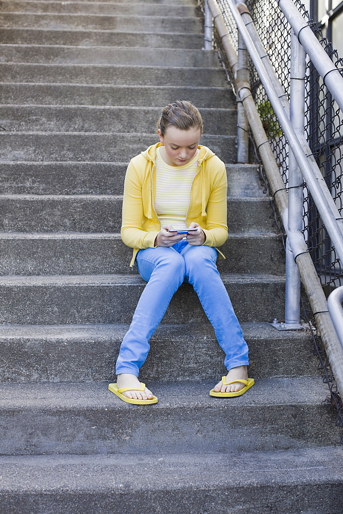Girl text messaging on steps