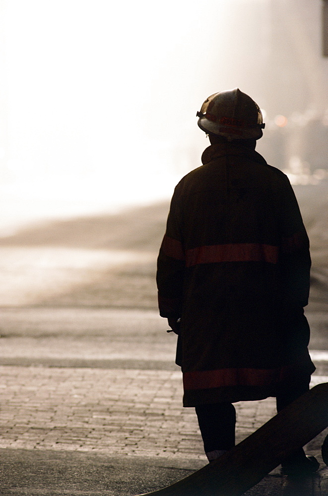 Silhouette of fireman looking at smoke in distance
