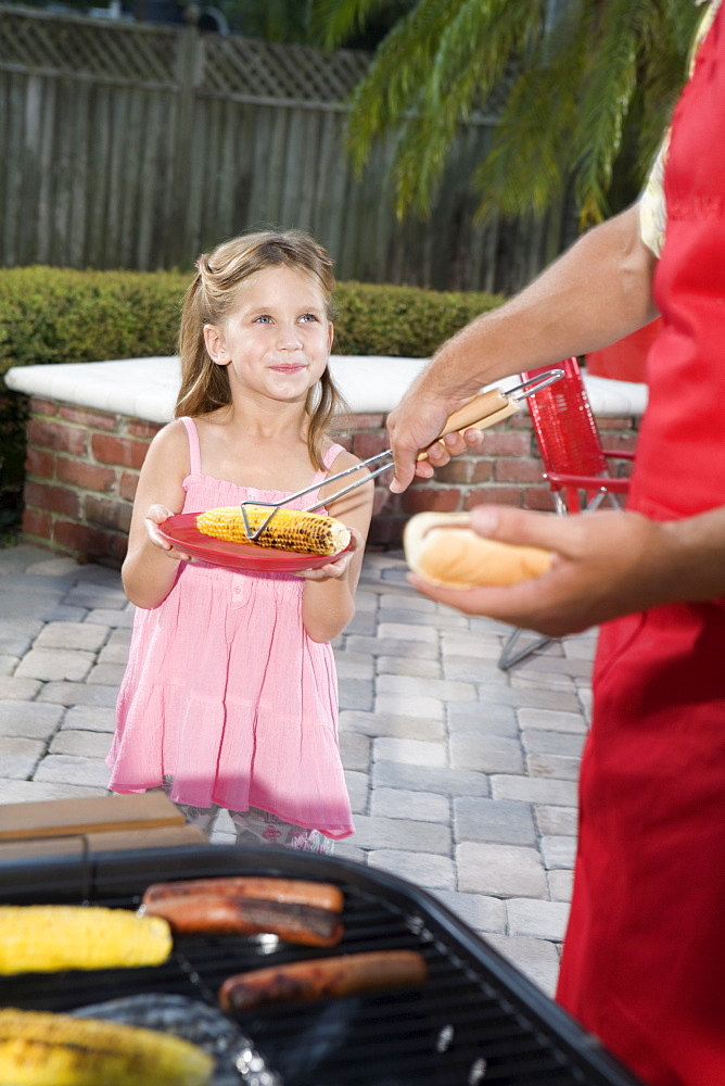 Father at barbecue grill serving daughter hot dog