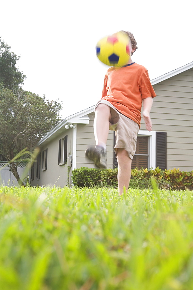 Boy in backyard kicking soccer ball