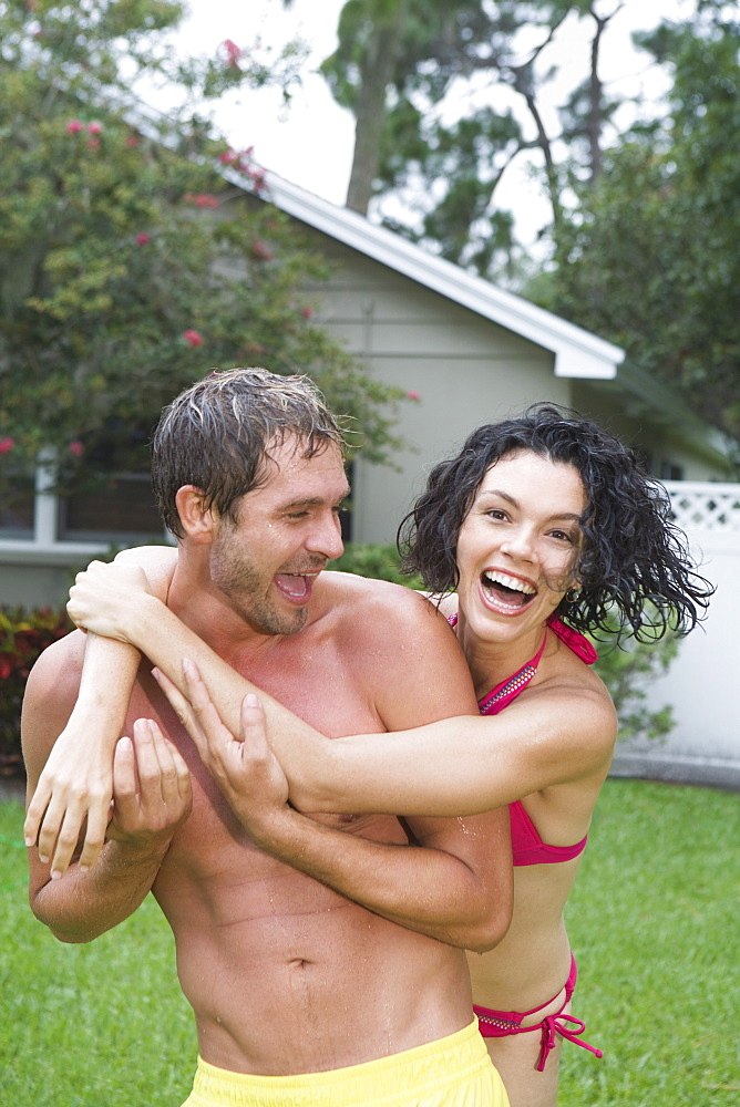 Couple in bathing suits hugging in backyard