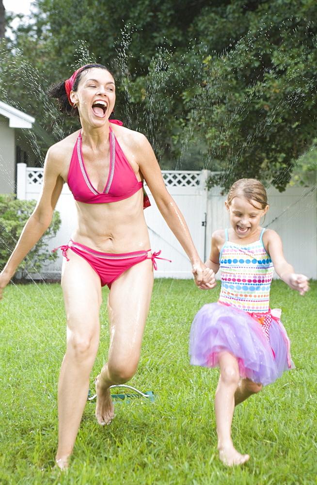 Mother and daughter running through sprinkler
