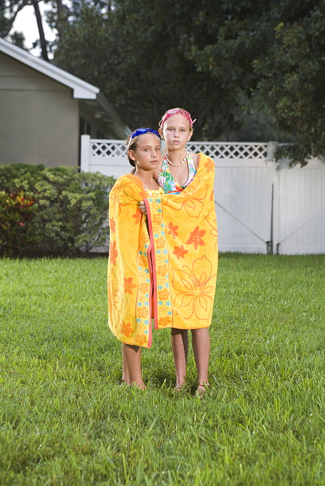 Portrait of sisters wrapped in towel standing in backyard