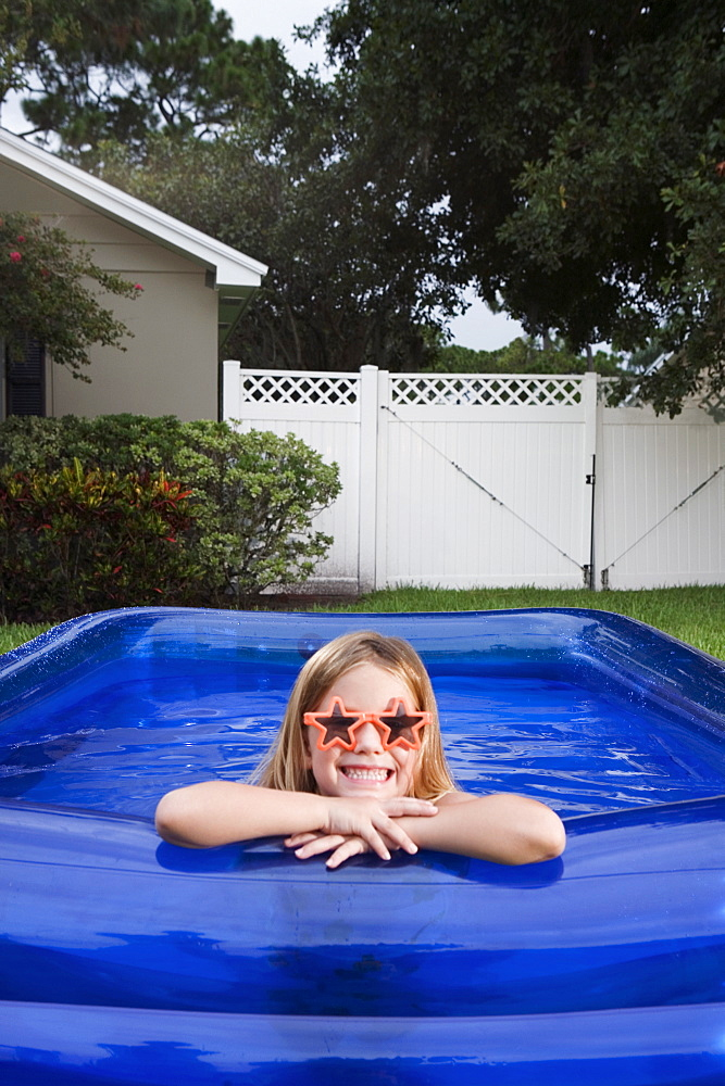 Girl leaning on edge of inflatable swimming pool