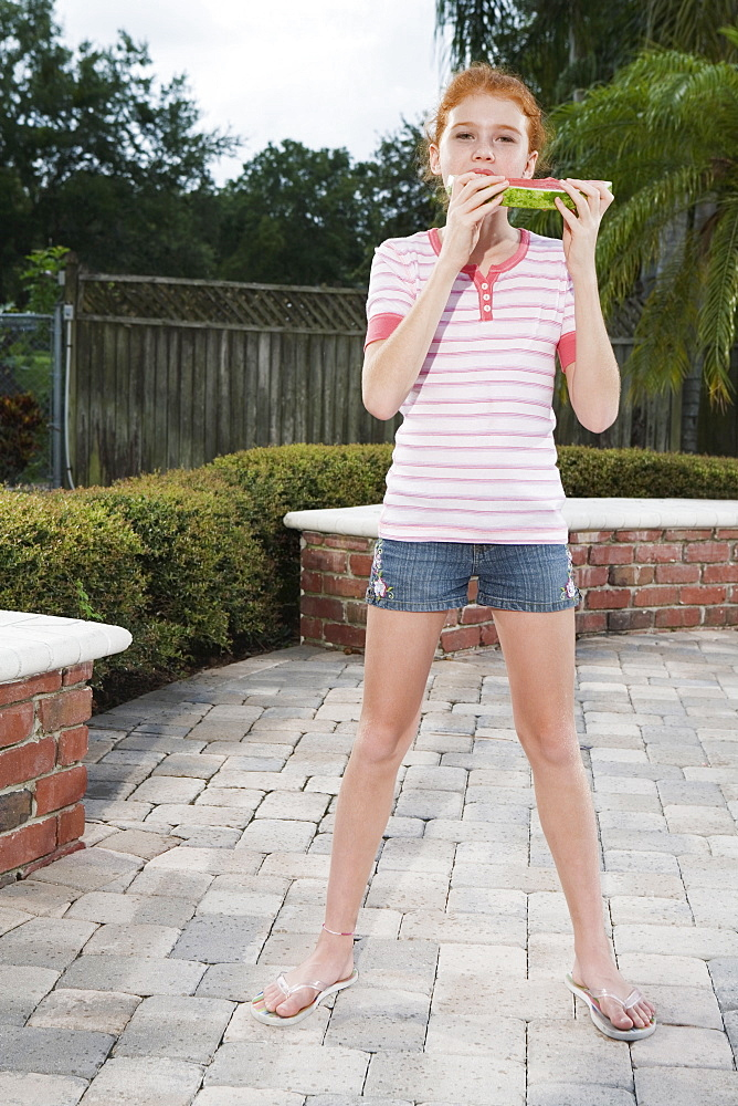 Girl eating watermelon on patio