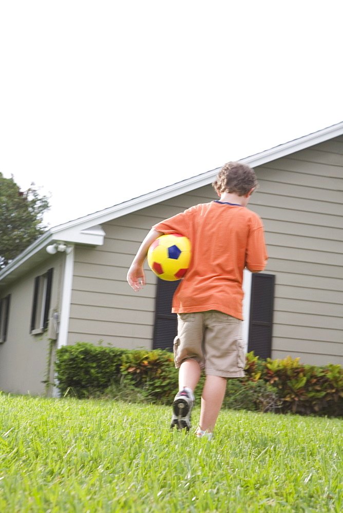 Boy carrying soccer ball in backyard