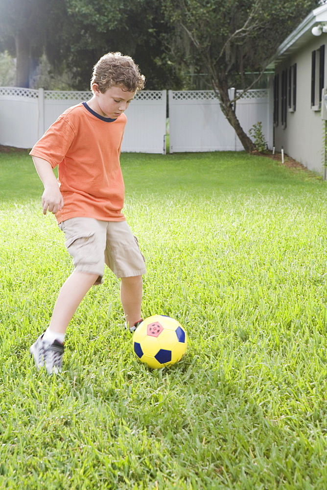 Boy playing in soccer in backyard