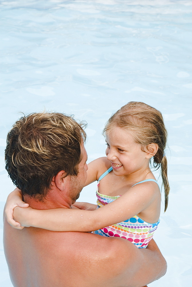 Father hugging daughter in swimming pool