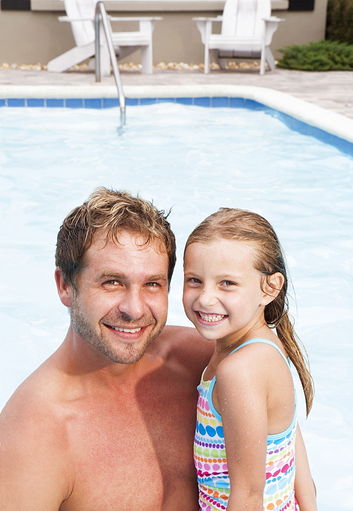 Father and daughter posing by swimming pool
