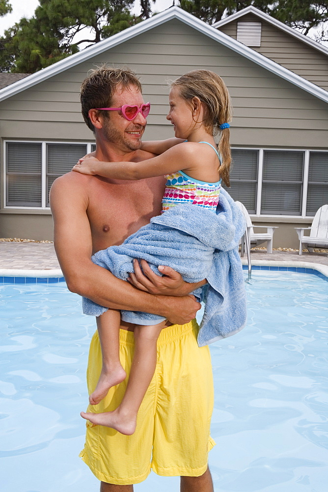 Father holding daughter by swimming pool