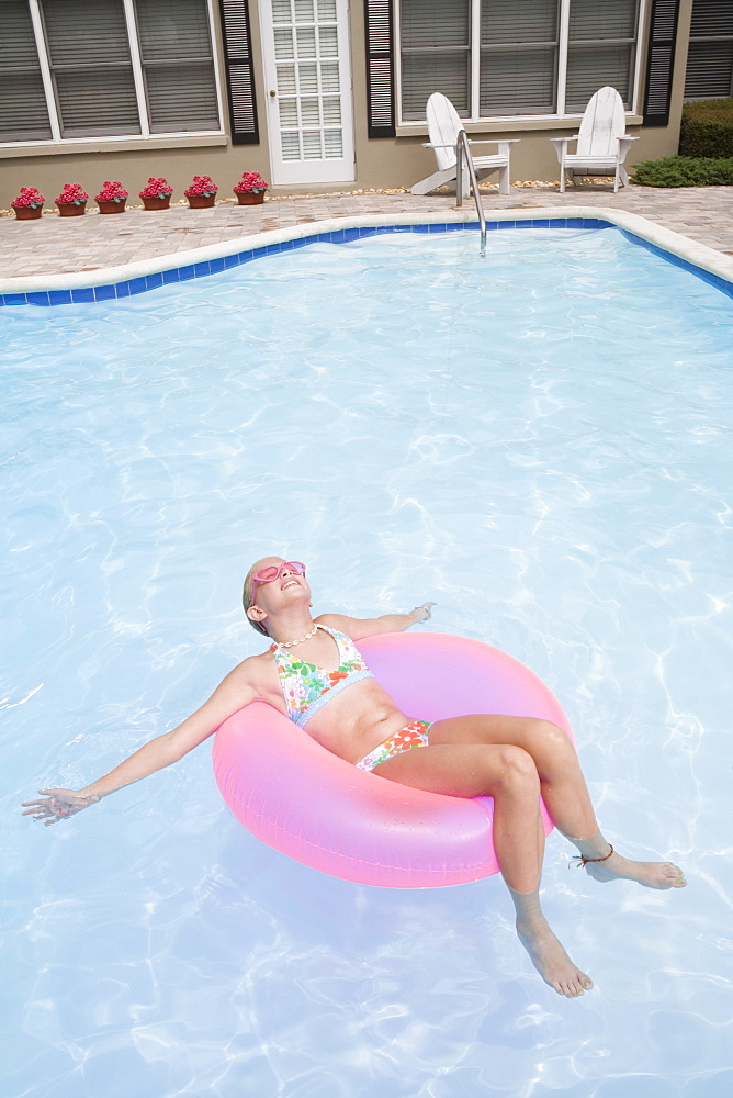 Girl relaxing on inflatable ring in swimming pool