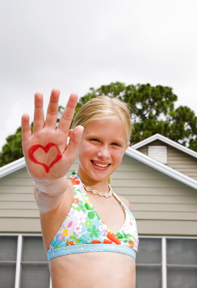 Girl holding out hand painted with heart design