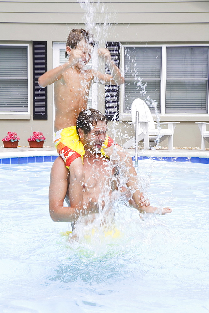 Father and son splashing in swimming pool