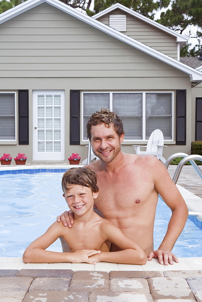Father and son posing in swimming pool