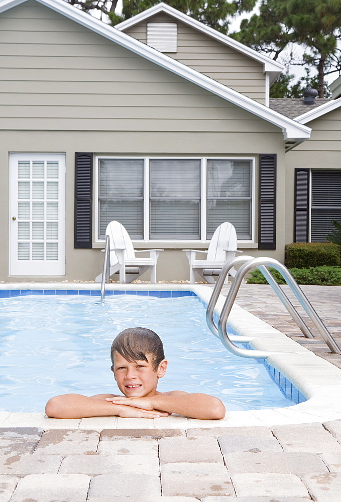Boy leaning on edge of swimming pool