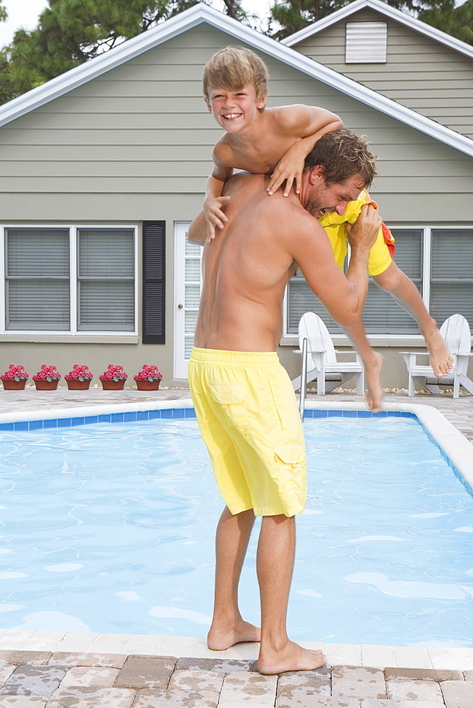 Father throwing son into swimming pool