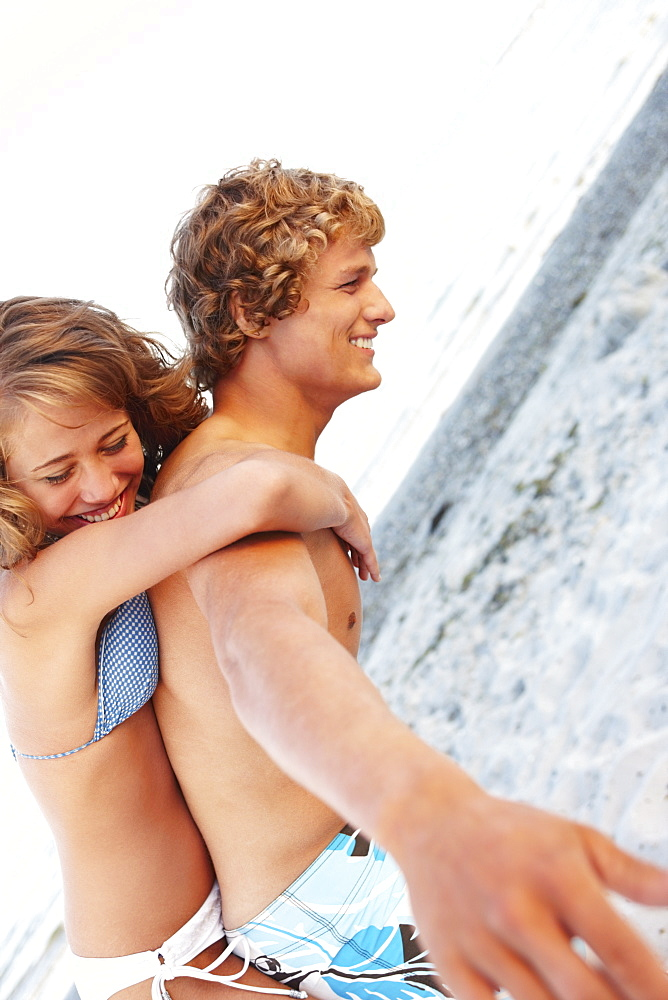 Young man carrying girlfriend on back