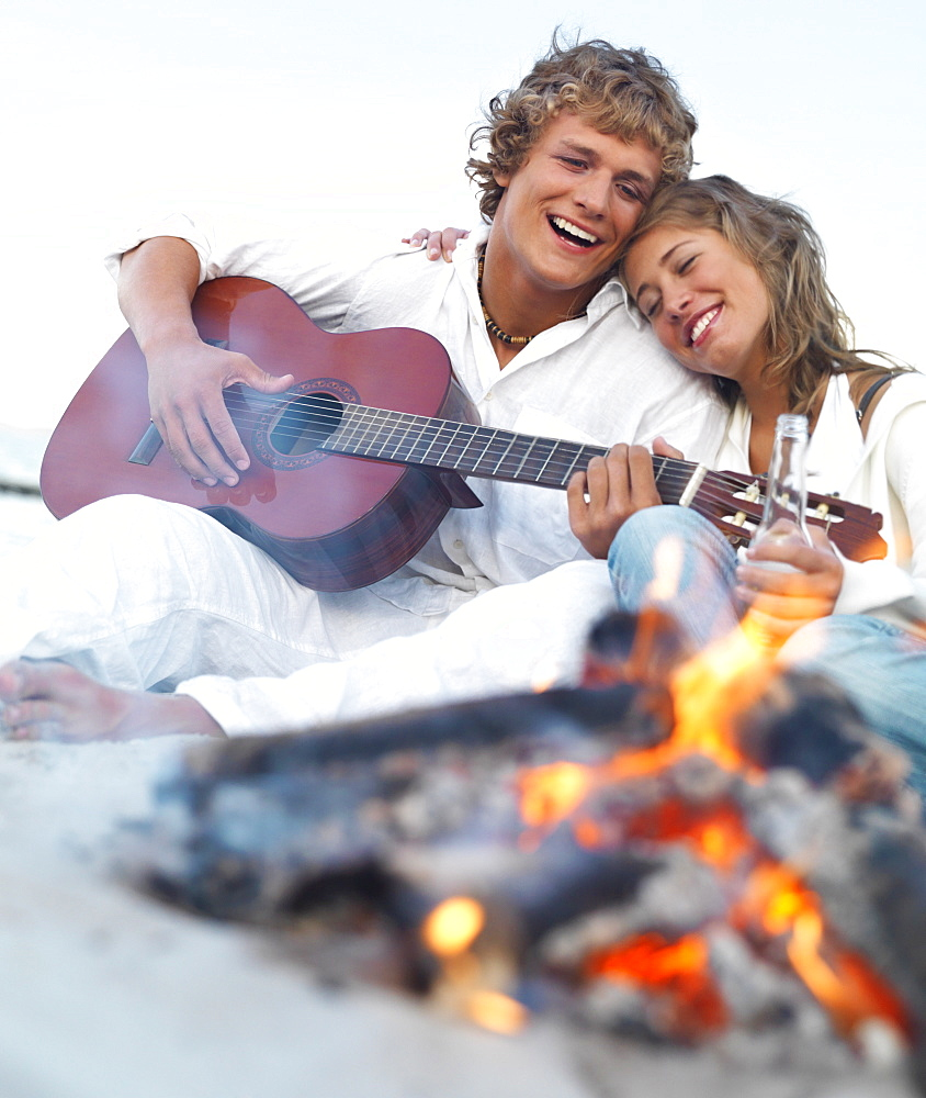 Young couple relaxing by campfire on beach