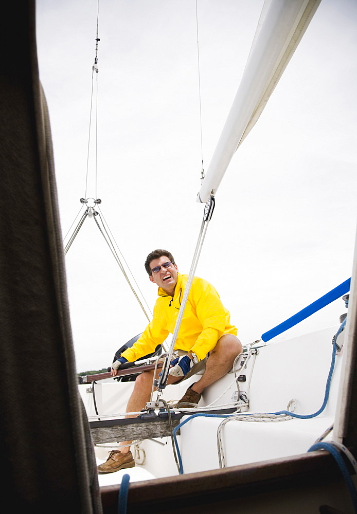 Man steering sailboat