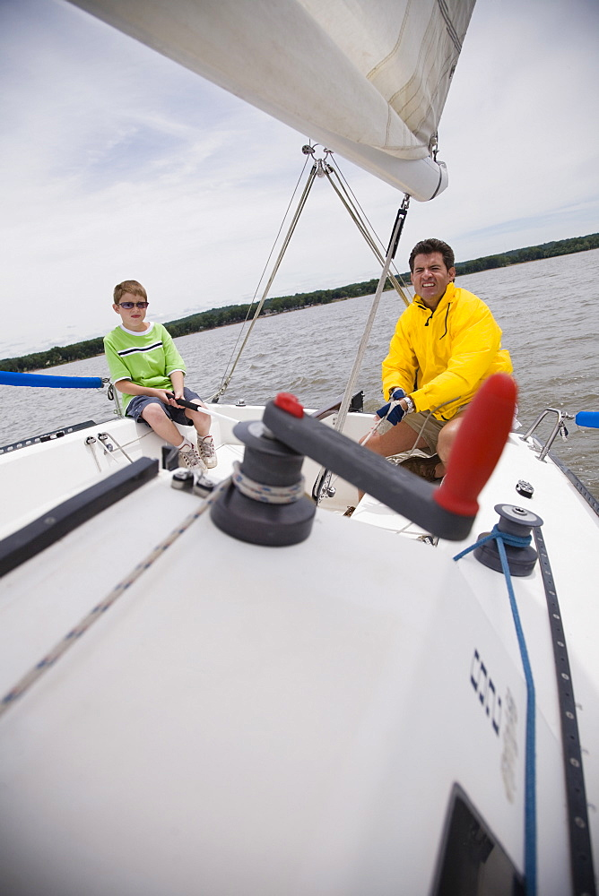 Father and son sitting on sailboat