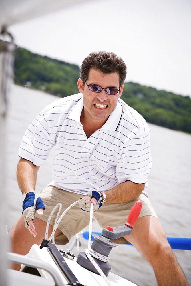 Man pulling rope on sailboat