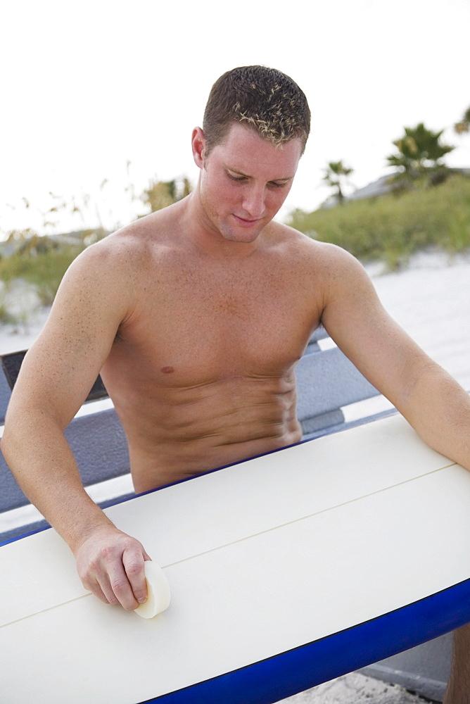 Man waxing surfboard