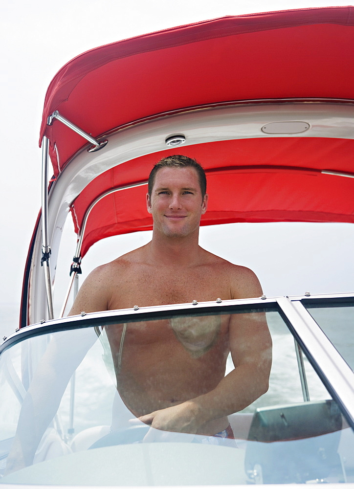 Bare-chested man driving boat