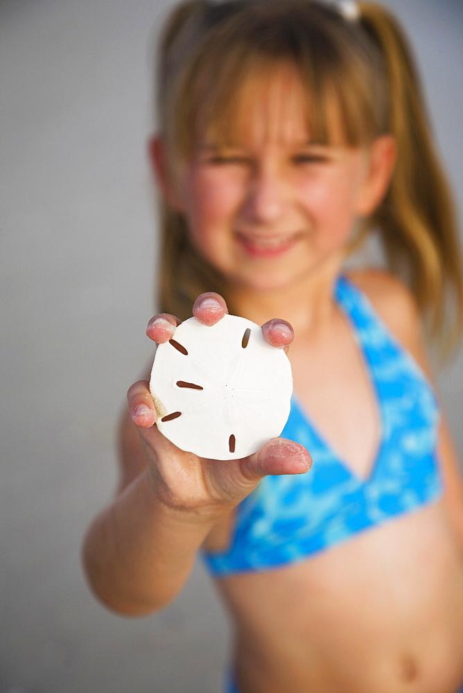 Girl holding up sand dollar, Florida, United States