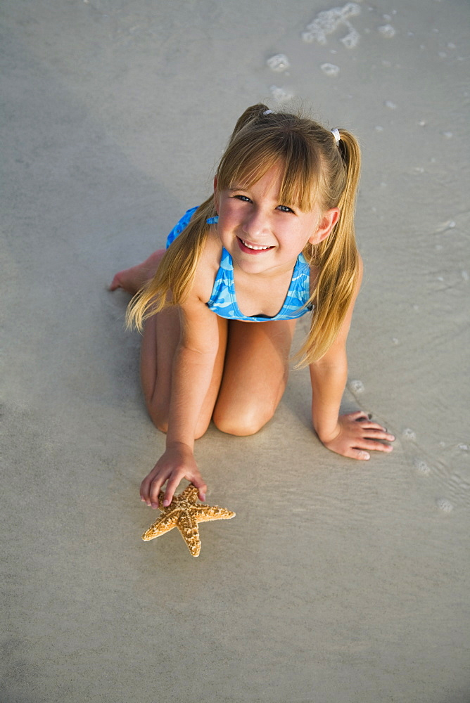 Girl picking up starfish, Florida, United States