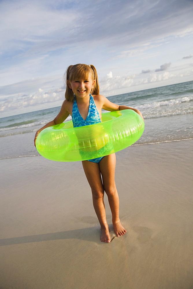 Girl in inner tube at beach, Florida, United States