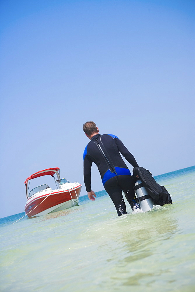 Man carrying scuba gear towards boat, Florida, United States