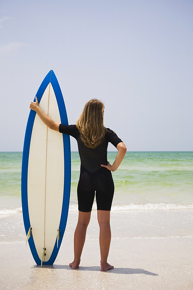 Girl holding surfboard in sand, Florida, United States