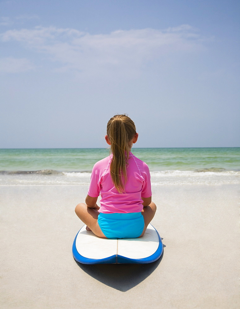 Young girl sitting on surfboard, Florida, United States